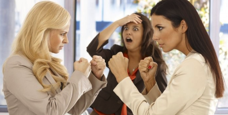 two business women with their fists raised with their colleague looking shocked behind them