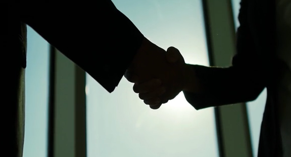 Two people silhouetted shaking hands