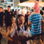 Girl with braids playing guitar on a busy street in wearing a school uniform. (out of focus to right- little boy in blue shirt on his father's shoulders looks at girl