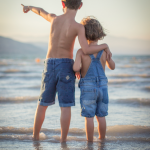 boy in jean shorts points across the sea with hand wrapped around younger child in denim overalls